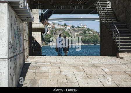 An old couple walk hand in hand under the iron brigde of Oporto, Portugal - Stock Photo