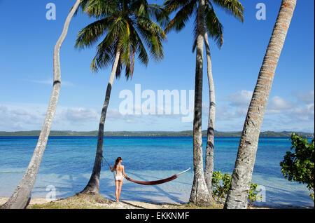Young woman in bikini standing by the hammock between palm trees, Ofu island, Vavau group, Tonga - Stock Photo