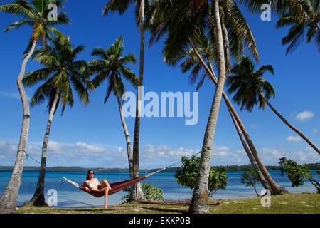 Young woman in bikini sitting in a hammock between palm trees, Ofu island, Vavau group, Tonga - Stock Photo