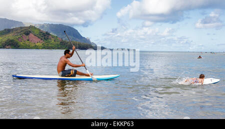 Father paddles after 2-year-old son kicking on boogie board  in Hanalei Bay on Kauai - Stock Photo