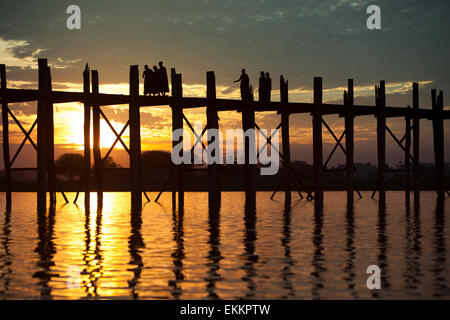 Silhouetted figures (Buddhist monks and locally dressed women,) on the U Bein bridge across Lake Taungthaman at - Stock Photo