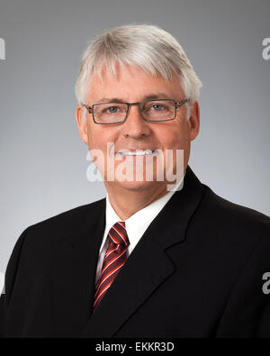 Studio portrait of mature businessman wearing black suit, against a gray background. - Stock Photo