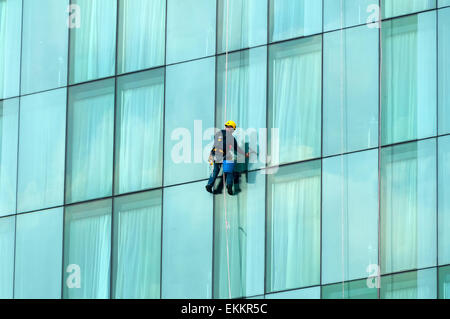 Window cleaner suspended on a rope on the Beetham Tower, Deansgate, Manchester, England, UK - Stock Photo