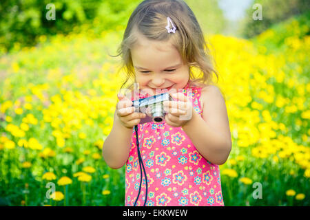 Little girl taking pictures on a meadow - Stock Photo