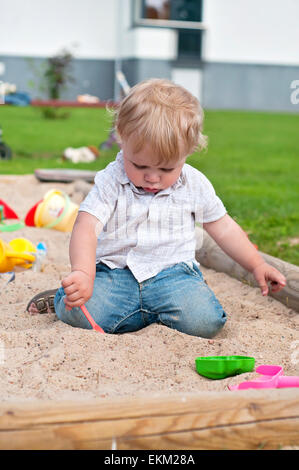 Child playing on playground in sandbox - Stock Photo