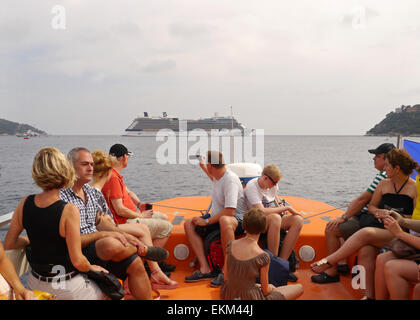A group of holidaymakers on a ship's tender with Celebrity Equinox in the background - Stock Photo