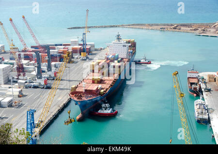 Cargo ship being escorted into port by tugs, Napier, Hawke Bay, North Island, New Zealand - Stock Photo