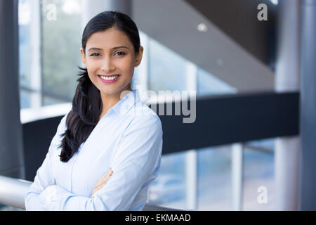 Closeup portrait, young professional, beautiful confident woman in blue shirt, arms crossed folded, smiling isolated - Stock Photo