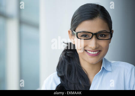 Closeup portrait, young professional, beautiful confident adult woman in blue shirt, with black glasses, smiling - Stock Photo