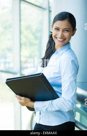 Closeup portrait, young professional, beautiful confident woman in blue shirt, holding coffee and black notebook - Stock Photo