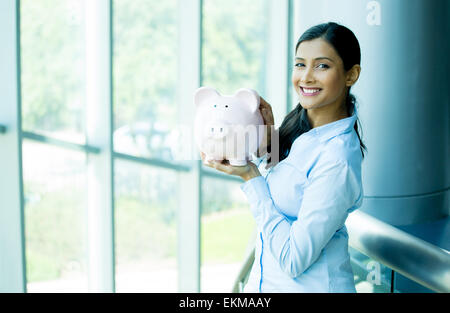 Closeup portrait happy, smiling business woman, holding pink piggy bank, isolated indoors office background. Financial - Stock Photo