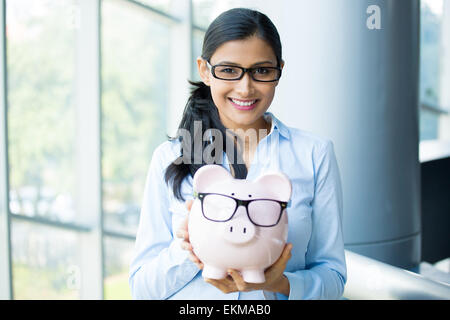 Closeup portrait happy, smiling business woman, holding pink piggy bank, wearing big black glasses isolated indoors office