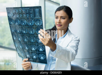 Closeup portrait of intellectual woman healthcare personnel with white labcoat, looking at full body x-ray radiographic - Stock Photo