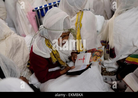 Ethiopian Orthodox worshiper reading the bible in Amharic during 'Holy Fire' ceremony inside the Ethiopian church - Stock Photo