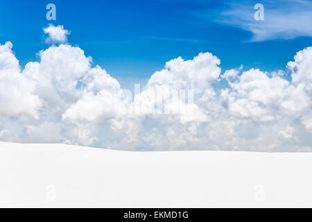 Snow covered mountain landscape with blue sky and fluffy cloud - Stock Photo