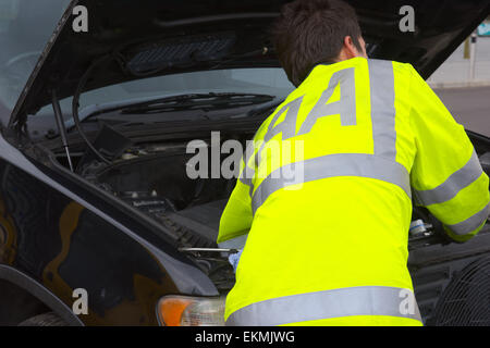 AA roadside assistance mechanic working on broken down car - Stock Photo