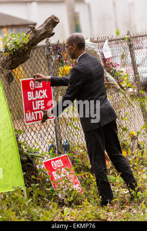 An activist adds signs to a makeshift memorial wall on the spot where unarmed motorist Walter Scott was gunned down - Stock Photo