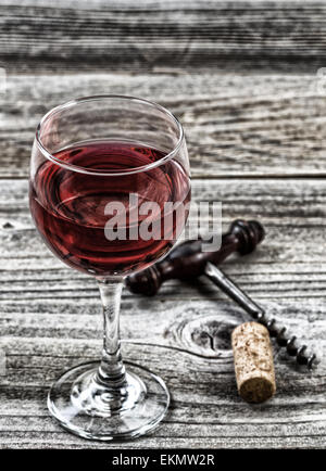 Vintage concept wine, focus on front lip of glass, with antique corkscrew and cork in background on rustic wood. - Stock Photo