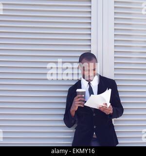 stylish black man documents handling outdoors - Stock Photo