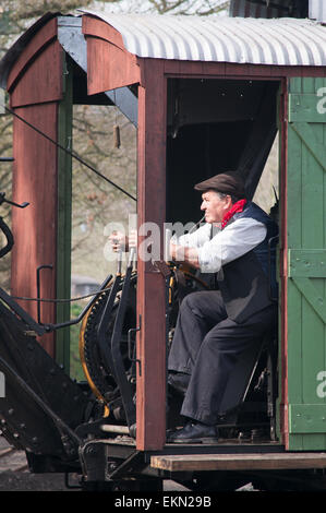 Man operating Erie steam excavator at Great North Steam Fair, Beamish Museum, England UK - Stock Photo
