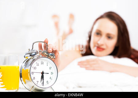 woman turns off the alarm - Stock Photo
