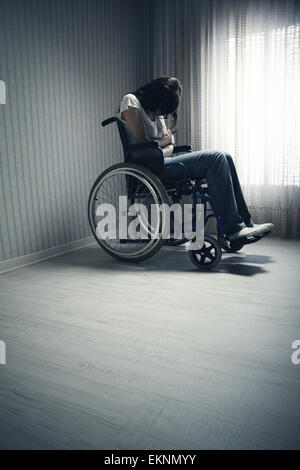 Crying woman sitting in wheelchair - Stock Photo