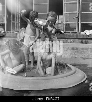 Children of Alexandra Day Nursery near Loch Lomond, Scotland cool off in a portable swimming pool on a hot summer's - Stock Photo