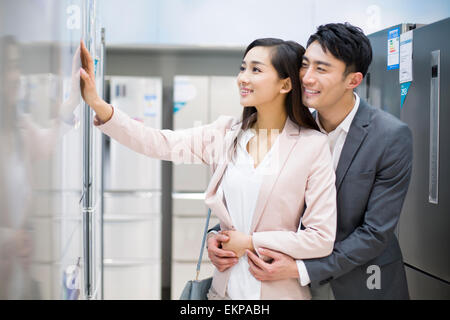 Young couple buying refrigerator in electronics store - Stock Photo
