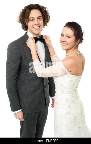 Pretty bride adjusting her man's bowtie - Stock Photo