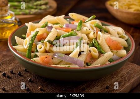 A delicious smoked salmon pasta with penne, asparagus, crushed black pepper, olive oil, and dill. - Stock Photo