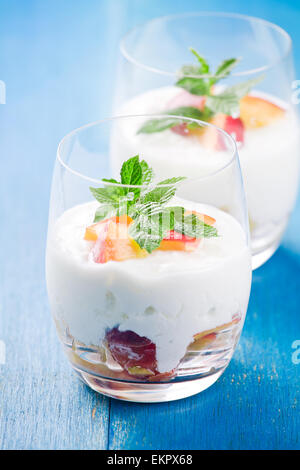 Close up photograph of a glass of yogurt with pieces of peach - Stock Photo
