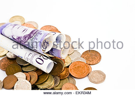 Rolled up 20 pound notes with coins on white background with copy space - Stock Photo