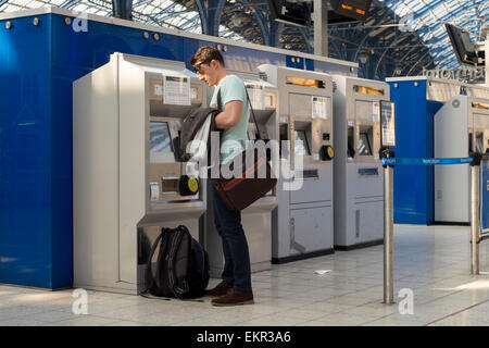 Commuter buying a rail ticket from a self service machine at Brighton Station - Stock Photo