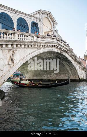 A traditional gondola under the Rialto bridge in Venice - Stock Photo