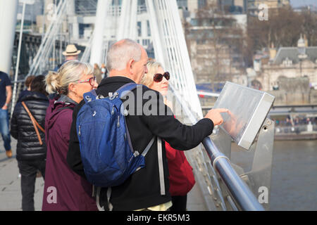Tourists studying a landmark map on the Golden Jubilee Bridge over the Thames in London - Stock Photo