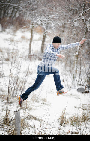 A man leaping from one post to another in the snowy woodland. - Stock Photo