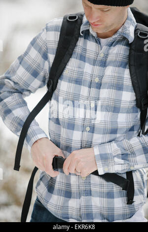 A man, a hiker fastening the belt securing his backpack. - Stock Photo