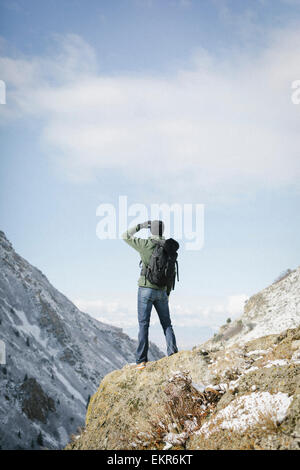 A man hiking in the mountains standing on an outcrop looking at the view. - Stock Photo
