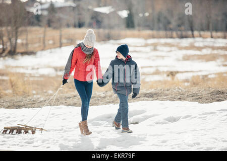 A brother and sister in the snow, one pulling a sledge. - Stock Photo