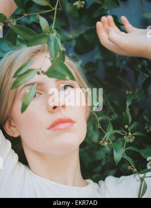 A blond haired woman looking wistfully through a vine with green leaves. - Stock Photo