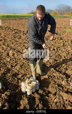 Researcher carrying out soil test by taking manual earth core samples from field with metal corer - Stock Photo