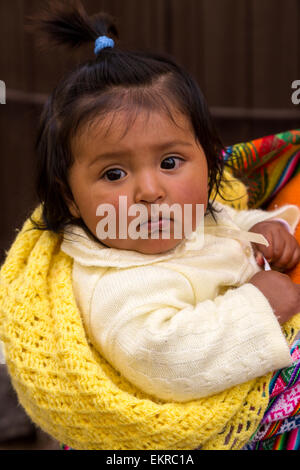 Peru, Cusco.  Young Quechua Girl being Carried on her Mother's  Back. - Stock Photo