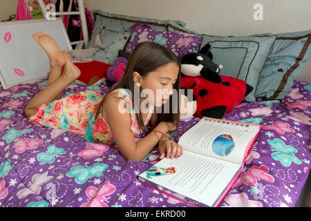 8 year old girl reading a story on her bed at home. - Stock Photo