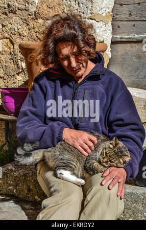 woman sitting on the steps of stone stairs stroking a brown speckled cat snuggling on her lap - Stock Photo