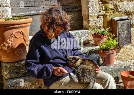 woman sitting on the steps of stone stairs with a brown speckled cat snuggling on her lap - Stock Photo