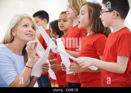 Children In Singing Group Being Encouraged By Teacher - Stock Photo