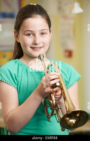 Girl Learning To Play Trumpet In School Music Lesson - Stock Photo