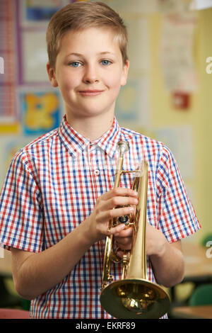 Boy Learning To Play Trumpet In School Music Lesson - Stock Photo