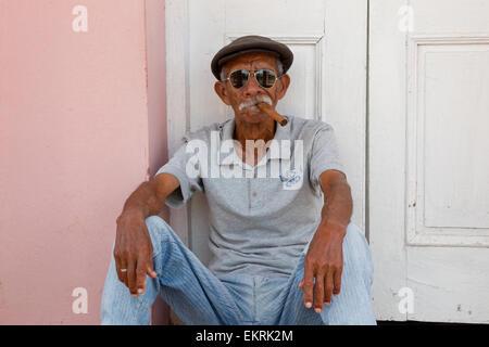 Cuban man with sunglasses smoking a cigar in a doorway - Stock Photo