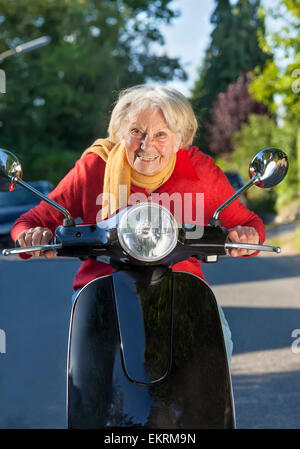 Elderly lady having fun on her scooter crouching low of the handlebars with a playful smile as she approaches the - Stock Photo